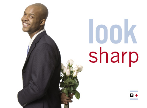 a smiling black man in a suit holding a bunch of white roses behind his back, captioned 'look sharp'