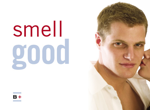 a white man in a white shirt looks at the camera as a woman's lips enter the frame to kiss him, captioned 'smell good'